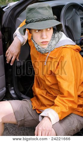 Young girl sitting at a car and looking for something