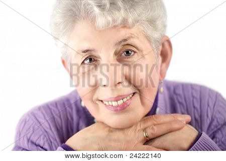 Senior woman portrait, close-up,with white hair and violet pullover, hands under shin,isolated on white background