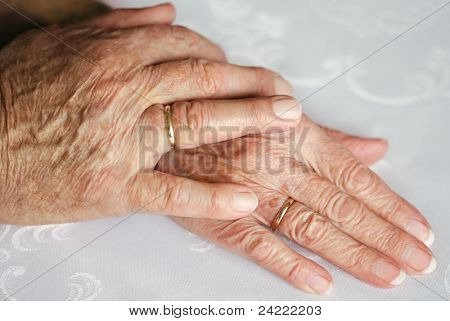 Two hands of an old couple, lying upon each other, with golden wedding rings
