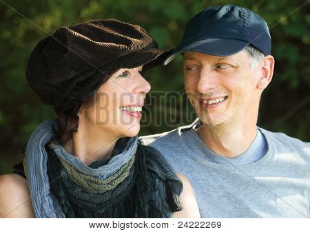 Middle-age couple with scarf and cap smiling at each other, outdoors