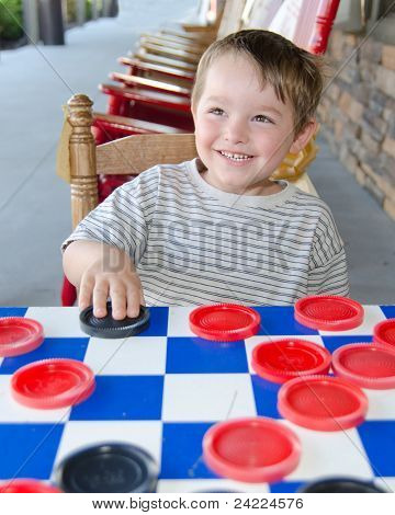 Smiling young boy playing checkers while sitting on rocking chair on porch