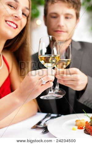 Couple for romantic Dinner or lunch in a gourmet restaurant drinking wine and eating