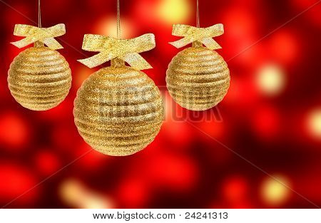Three Golden Balls Over Abstract Background Of Red Holiday Lights