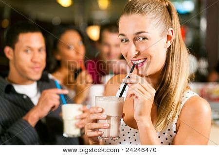 Friends drinking milkshakes in a bar and have lots of fun; focus on the woman in front