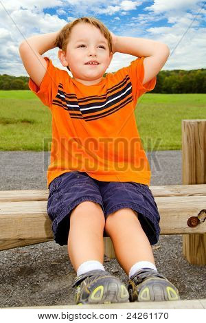 Young boy does sit-ups while exercising outdoors at playground.