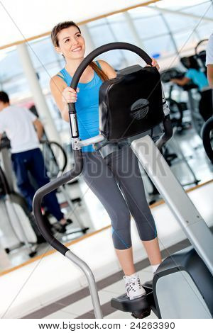Girl working out at the gym in an xtrainer