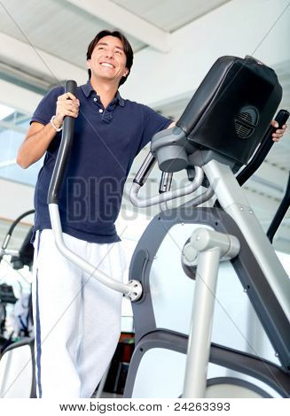 Man exercising at the gym in a xtrainer