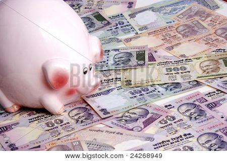 Indian currency notes and piggy bank