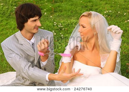 Beautiful young groom and bride wearing white dress sitting on green grass and handcuffed,  groom ask of bride key