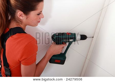 woman fixing something on a wall