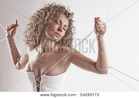 Menina de vestido branco, com as mãos amarradas com corda