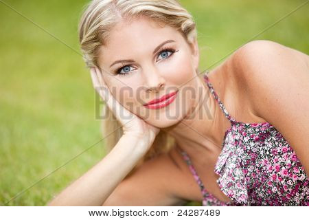Beautiful young woman sitting in the grass