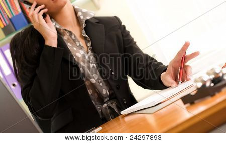 Portrait of a beautiful young businesswoman calling by phone in office