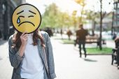Lady Is Standing In The Street And Hiding Face Behind Upset Emoticon With Falling Tear. Sadness Conc poster