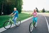 Mature Caucasian Couple Riding Bicycle Laughing And Getting Joy From Outdoor Activities. Retired, Ac poster