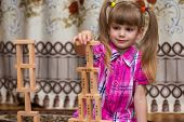 Girl Play With Wooden Blocks. Kid Inspecting Wooden Block Buildings, Childhood Activities. Tower Sta poster