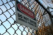 stock photo of barbed wire fence  - danger do not enter sign on fence topped with barbed wire - JPG
