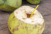 Opened Coconut With Straw Ready For Drinking. Fresh Coco Water Photo. Coconut Fruit On Wooden Table. poster