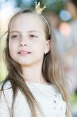 Girl Kid On Calm Face With Tiny Golden Crown On Head, Nature Background, Defocused. Girl Princess Wi poster