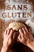 high-angle shot of a young man kneading a piece of dough on a wooden table sprinkled with a gluten f poster