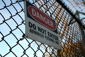 image of barbed wire fence  - danger do not enter sign on fence topped with barbed wire - JPG