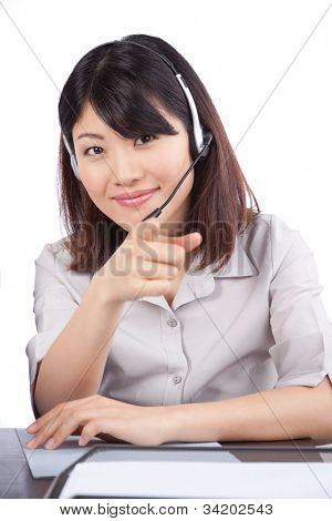 Businesswoman wearing a headset pointing finger isolated on white background.