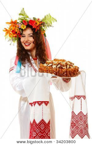Beautiful ukrainian young hospitable woman in garland and native costume by tradition holding embroidered towel and round loaf, on white background