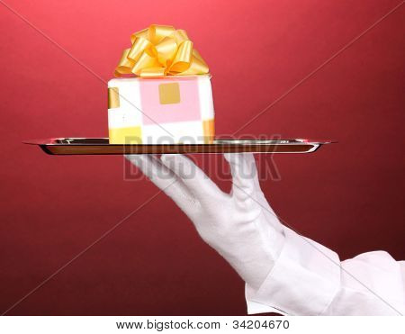 Hand in glove holding silver tray with giftbox on red background