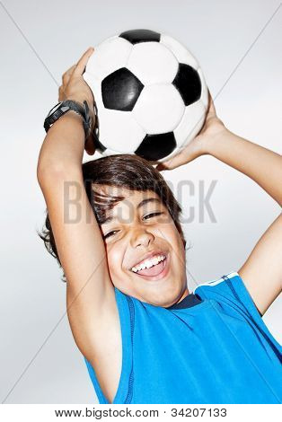 Happy jumping boy, cute kid playing football, active child, young male teen goalkeeper enjoying sport game, catching ball, isolated closeup portrait, preteen smiling and having fun, little footballer