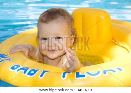 Beautiful Baby Girl Enjoying The Warm Water In The Family Pool