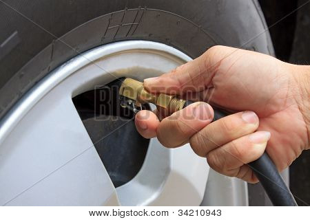hand and vehicle wheel add air pressure