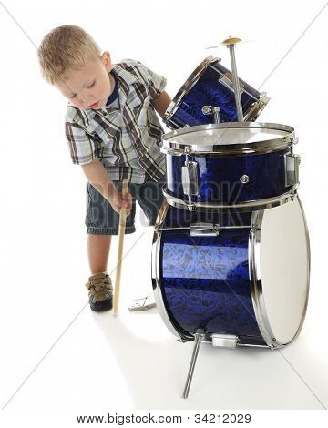 An adorable preschooler bending over a drum set to beat the base drum with a drumstick.  On a white background.