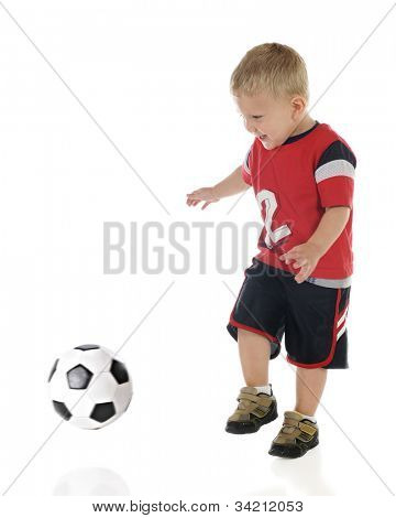 An adorable 2-year-old prepared to kick an approaching soccer ball.  Motion blur on ball and child's legs.  On a white background.
