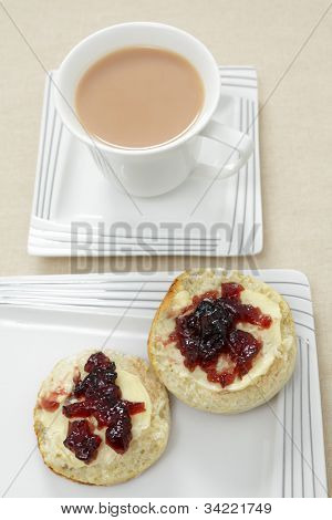 A traditional English afternoon tea of a scone topped with butter and blackcurrant jam and a cup of milky tea.