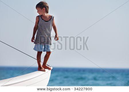 young happy boy on board of sea yacht