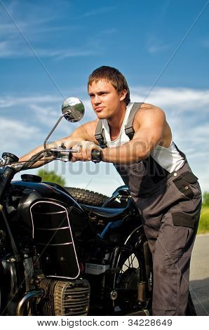 Handsome Man In A Boilersuit Rolling A Motorcycle.