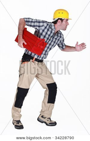Builder stood in running position holding tool box