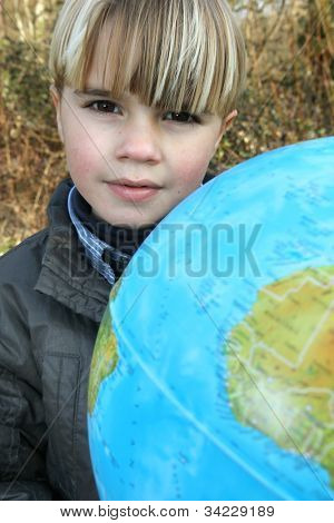 Little boy stood outdoors with globe