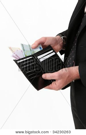 Businessman pulling out a wad of money from his wallet