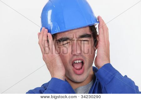 A young manual worker hearing unbearable noise.