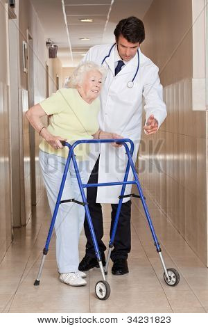 A doctor assisting a senior woman onto her walker.