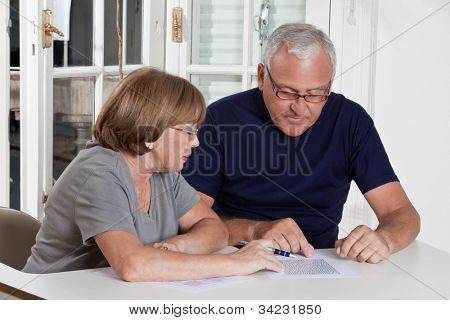Portrait of mature couple playing scrabble game.