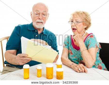 Senior couple shocked by the high cost of their medical bills.  White background.
