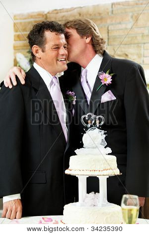 One groom at a gay marriage kissing his husband lovingly on the cheek.