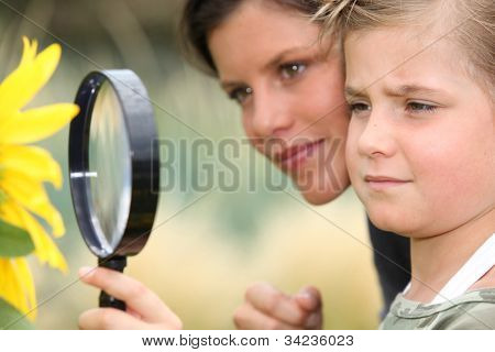Girl with magnifying glass watching flower