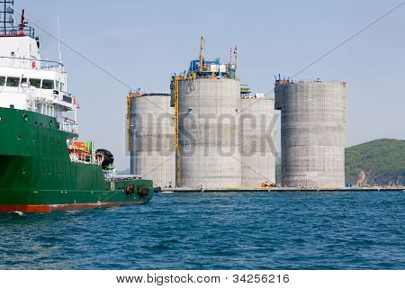 Ocean tug towing base offshore oil drilling platform. Sea of Japan. Russian coast.