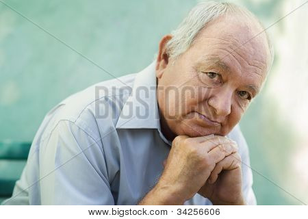 Portrait Of Sad Bald Senior Man Looking At Camera