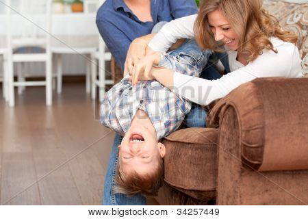 Happy parents tickling son and fun laugh