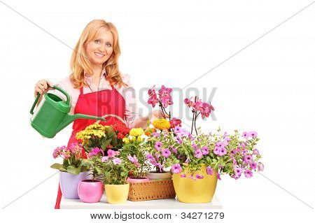 A beautiful female florist holding a can and watering flowers isolated on white background