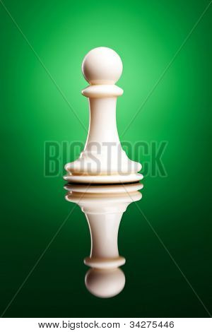 Photo of a single chess piece - a white king. The chess piece on green background